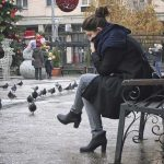 Picture of a woman on a park bench in a town square. Her head is on her hand and she is struggling from the pain and solitude associated with grief from loss. Grief During the Holidays - Living Beyond Our Pain Points - The holiday season can be a sad and difficult time for those struggling with grief from personal loss. If you, or someone you know, is struggling with grief or loss contact us at Barrington Behavioral Health and Wellness. Phone: 888-261-2178 or email: help@barringtonbhw.com