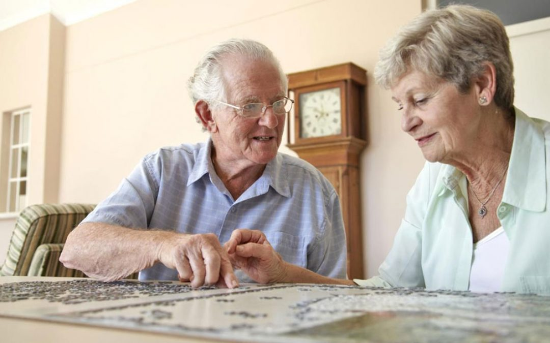 Picture of elderly couple assembling a jigsaw puzzle - Dementia in our loved ones can be frustrating. Download our e-booklet to learn what you can do to help others live with dementia.