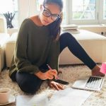 Picture of a young woman in glasses sitting on the living room floor with her laptop computer and a cup of coffee and papers working on her holiday budget. Budgeting for next year's holiday spending. Follow these steps throughout the year to be prepared to spend what you need, when you need, and cover all your gift giving for next holiday season. Do you have problems saving money or spending too much? Think you may need help? Contact Barrington Behavioral Health and Wellness at 888-261-2178