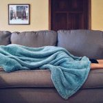 Image of a man laying on a couch hidden under a blanket, apparently asleep, likely depressed by the events of sheltering in place during the coronavirus. If you are feeling anxious and isolated, we can help. Call Barrington Behavioral Health and Wellness at 888-261-2178 or email help@barringtonbhw.com