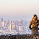 Picture of a young woman sitting on a stone wall overlooking a large city in the valley, it is dawn and she contemplates the future in the 'new normal' that is life during, and after, COVID-19. Contact Barrington Behavioral Health and Wellness to find out how you can learn to accept, and flourish, in the 'new world' 'AC' - After Coronavirus. Call 888-261-2178
