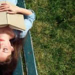Image of a young woman laying on a park bench, sun shining down on her face, book open and laid across her chest, her hands across the opened book. She is serene. Finding compassion in trying times requires but breathing and mindfulness. Brittany Salvador, LCPC, gives suggestions how to find these essential qualities in you. Call Barrington Behavioral Health and Wellness for more information: 888-261-2178