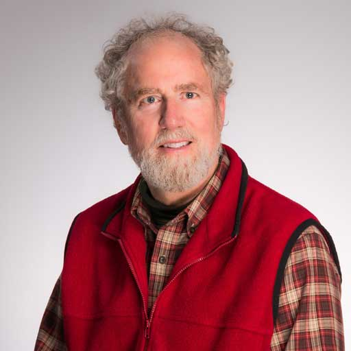 Picture of Michael Hugo, MAPS, MSW, LCSW wearing a plaid shirt and red vest.