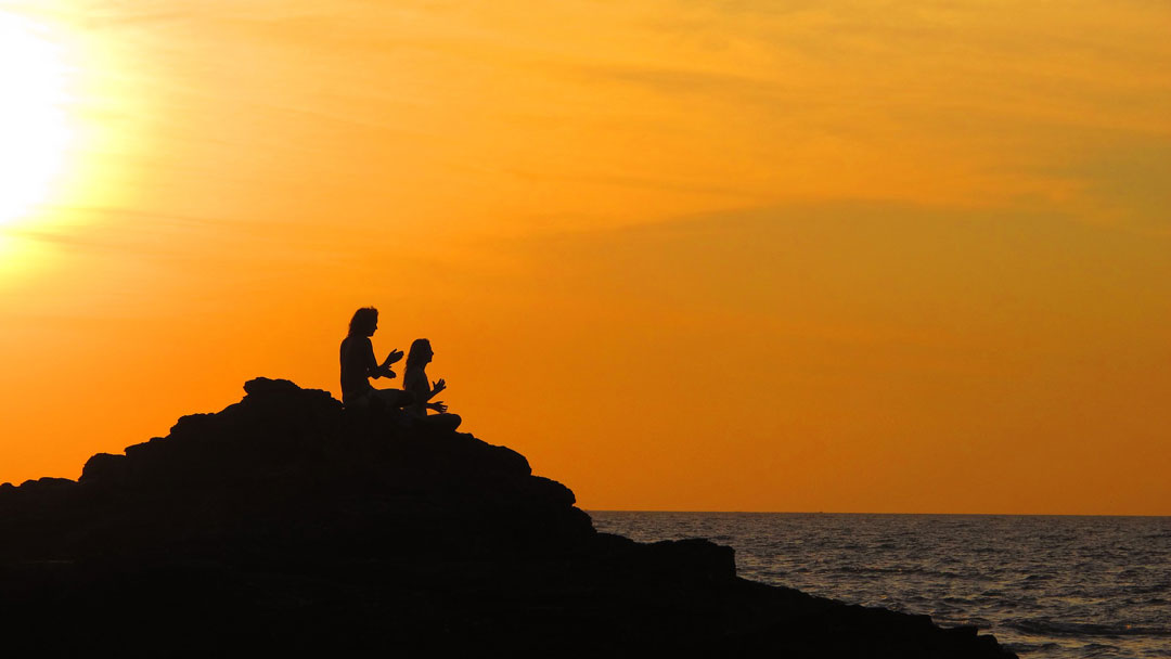 Picture of a man and woman sitting in silhouette on a rocky slope beside the seashore hands at chest height - channeling energy in meditation, sun is setting to the right over their shoulders. Spiritual guidance and spirituality can be a beneficial addition to a healthy and productive psychotherapy program. Barrington Behavioral Health & Wellness creates individual, custom treatment that works for you. Phone: 888-261-2178.