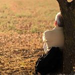 Serene image of a middle aged man with gray hair sitting on the ground leaning up against a small fruit tree. Serenity is the key, 10 things you may not have known about anger. Barrington Behavioral Health and Wellness; help@barringtonbhw.com phone: 888-261-2178